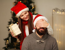 Happy girl gives her boyfriend a Christmas present Royalty Free Stock Images