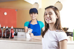 Happy Girl Giving Dollar Note To Waitress In Ice Cream Parlor Stock Photo