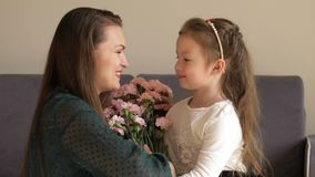Happy girl giving flowers and hugging her mother at home. Mother`s day concept