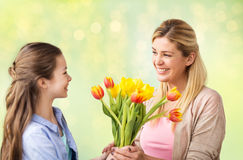 Happy girl giving flowers to mother over lights Stock Image
