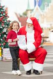Happy Girl Giving Letter To Santa Claus Stock Photography