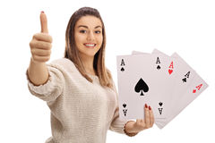Happy girl giving a thumb up and holding four aces Royalty Free Stock Photo