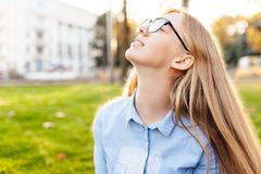 Happy girl with glasses breathe fresh air, enjoy the warmth, out. Side stock photo