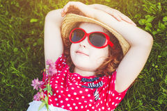 Happy girl with glasses lying on the grass in a summer park. Hap Stock Photography