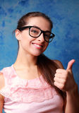 Happy girl in glasses showing thumb up sign Royalty Free Stock Photo