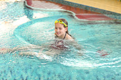 Happy girl with goggles in swimming pool. Happy girl with goggles relaxing in swimming pool Royalty Free Stock Photo