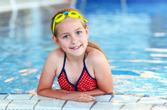 Happy girl with goggles in swimming pool. Cute girl with goggles in swimming pool Royalty Free Stock Image