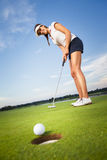 Happy girl golfer putting ball into hole. Smiling woman golf player putting successfully ball on green, ball dropping into cup, blue sky in background Stock Photos