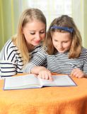 Happy girl and grandmother studying. Royalty Free Stock Photography