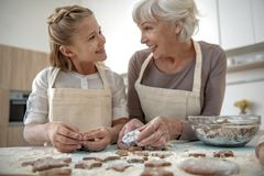 Happy girl and granny having fun in kitchen Royalty Free Stock Image