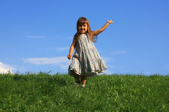 Happy girl on the grass. Running girl on the hill Royalty Free Stock Photography