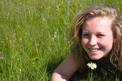 Happy girl in the grass. With a flower Stock Image