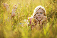 Happy girl in the grass looking up Stock Photos