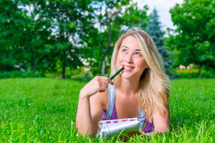 Happy Girl  on the grass with notebook and pe Royalty Free Stock Photography