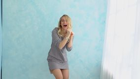 Happy girl in gray dress is dancing against a blue wall next to the window. Happy girl in gray dress is dancing against a blue wall next to the window stock footage