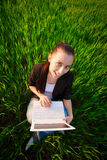 Happy girl in a green field with a laptop. summer Stock Images
