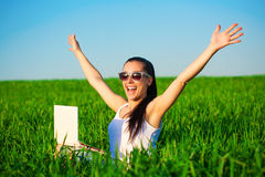 Happy girl in a green field with outstretched arms Royalty Free Stock Photography