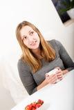 Happy girl in grey holding mug angled Stock Photo