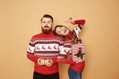 Happy girl and a guy dressed in red and white sweaters with deer hold Christmas gifts in their hands on a beige stock photo
