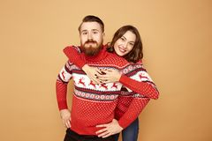 Happy girl and a guy dressed in red and white sweaters with deer are hugging on a beige background in the studio stock image
