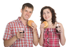 Happy girl and a guy eating hamburgers Royalty Free Stock Photos
