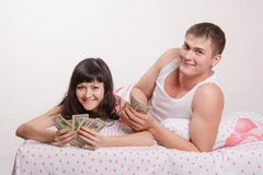 Happy girl and guy with wad of money in bed Stock Photography