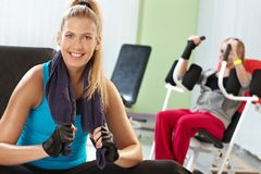 Happy girl at the gym. Happy attractive girl resting at the gym, smiling, sitting on exercise machine Royalty Free Stock Images