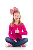 Happy girl with hair bow showing thumb up Stock Image