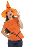 Happy girl in Halloween hat pointing on copy space Royalty Free Stock Images