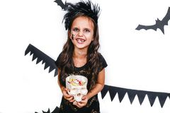 Happy girl in a halloween costume holding skull and having fun. Happy girl in a halloween wich costume holding skull and having fun stock images