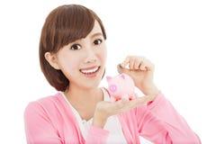 Happy girl hand putting coin into piggy bank stock photos