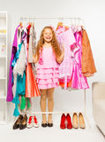 Happy girl between hangers with bright dresses Stock Images