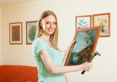 Happy girl hanging art pictures Royalty Free Stock Image