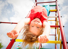 Happy girl hanging from a jungle gym in a summer garden Stock Images