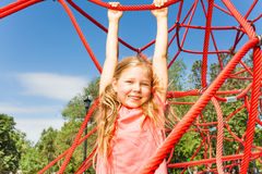Happy girl hanging on red rope of net outside Royalty Free Stock Photography