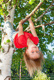 Happy girl hanging from a tree in a summer garden Royalty Free Stock Photos