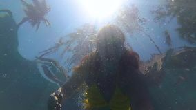 Happy girl happy swims underwater in the pool. Sunlight through the water stock footage