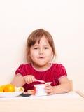 Happy girl has lunch with yogurt and mandarins royalty free stock photo