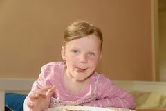 Happy girl has a snack in the kitchen. A cute small girl smiles. A small girl with chocolate cream stains on face Stock Image