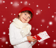 Happy girl in hat with box gift show fir tree wool toy on red Stock Images