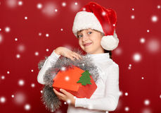 Happy girl in hat with box gift show fir tree wool toy on red background Stock Photos