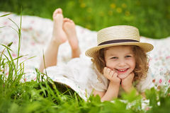 Happy girl in a hat lies and laughs Royalty Free Stock Photography