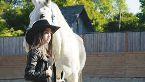Happy girl in hat poses with smile at white kind horse on arena stock footage