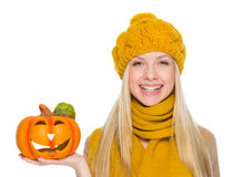 Happy girl in hat and scarf holding jack-o-lantern Royalty Free Stock Photos