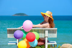 Happy girl in a hat sitting on a background sea. Stock Photo