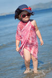 Happy girl in hat and sunglasses, walking near sea Royalty Free Stock Image