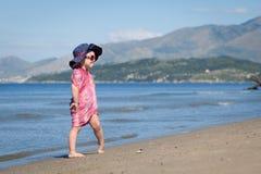 Happy girl in hat and sunglasses, walking near sea Stock Photo