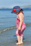 Happy girl in hat and sunglasses, walking near sea Royalty Free Stock Photo