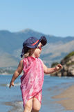 Happy girl in hat and sunglasses, walking near sea Stock Image