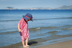 Happy girl in hat and sunglasses, walking near sea Royalty Free Stock Photography